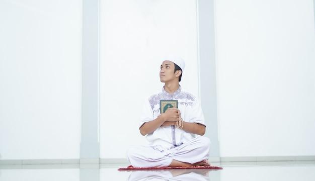Ein porträt eines asiatischen muslimischen mannes rezitieren in der moschee