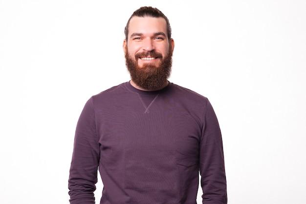 Ein porträt eines bärtigen jungen mannes, der lächelt und die kamera nahe einer weißen wand betrachtet
