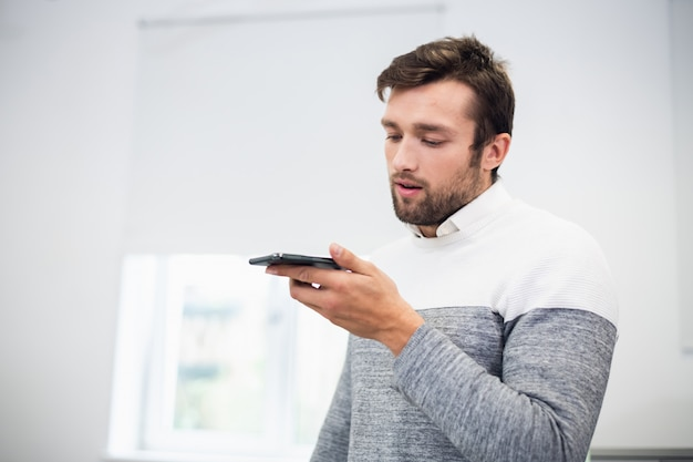 Ein porträt eines büroangestellten, der mit jemandem spricht, der den lautsprechermodus auf seinem telefon verwendet