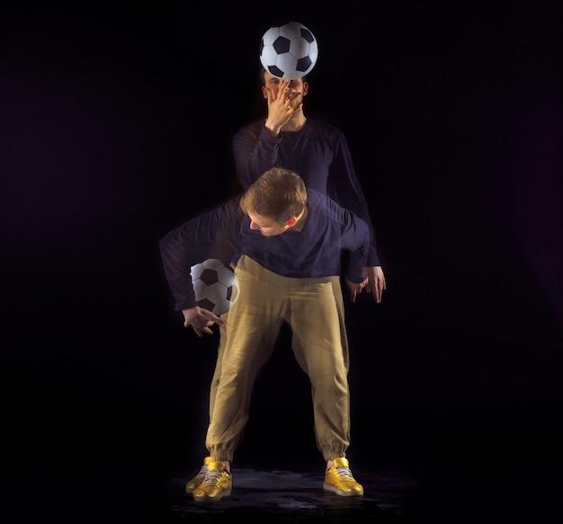 Ein porträt eines fans mit ball auf grauem studiohintergrund. freestile