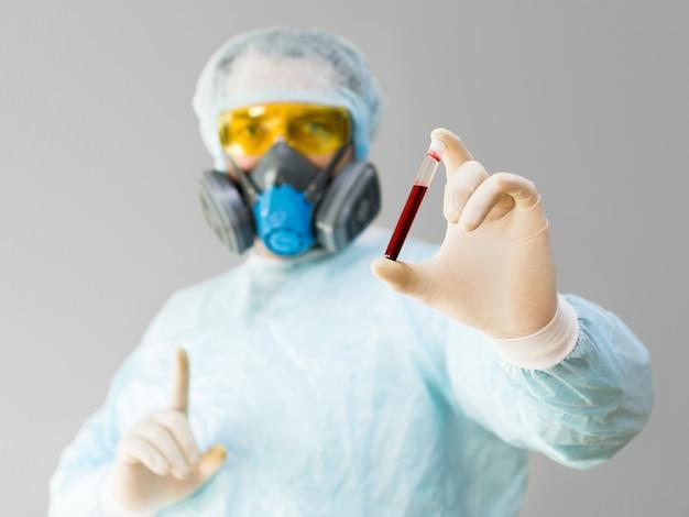 Ein porträt eines forschers in einem medizinischen kittel und einer schutzmaske, der ein reagenzglas mit erkranktem b...