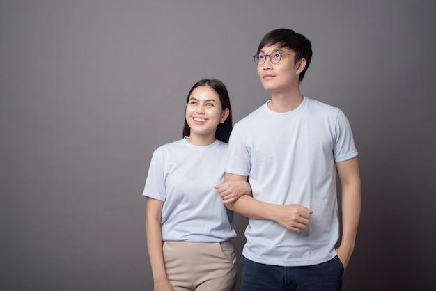 Ein porträt eines glücklichen paares, das ein blaues hemd trägt, umarmt sich grau