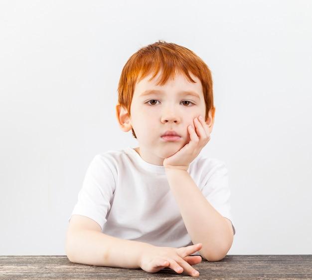 Ein porträt eines jungen, der müde den kopf mit der hand über das kinn hält