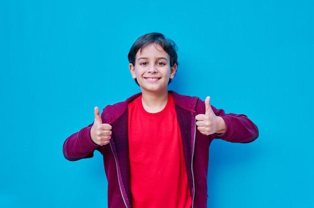 Ein porträt eines jungen in t-shirt und jacke mit daumen beider hände nach oben