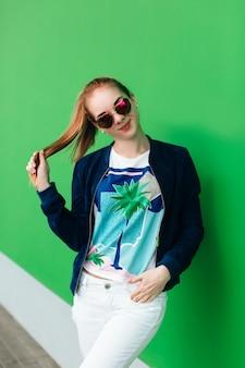 Ein porträt eines jungen mädchens in der blauen jacke im freien nahe grüner wand mit weißer linie nach unten. das mädchen trägt eine sonnenbrille, hält den haarschwanz in der hand und schaut in die kamera.