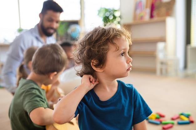 Ein porträt eines kleinen jungen mit klassenkameraden und lehrer drinnen im klassenzimmer