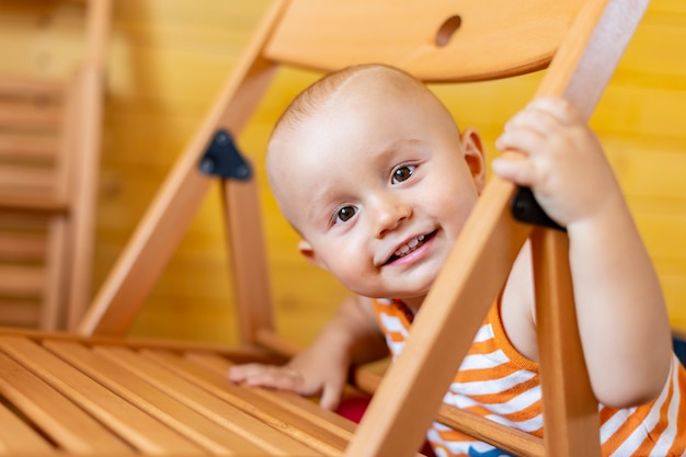 Ein porträt eines niedlichen entzückenden lachenden lächelnden jungen, der hinter einem stuhl heraus schaut, der eine ärmellose gestreifte orange spitze trägt.