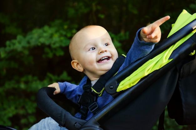 Ein porträt eines niedlichen glücklichen lächelnden jungen, der im kinderwagen sitzt, der zur seite schaut und finger oben im park während des spaziergangs im sommer zeigt.