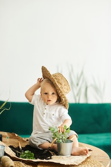 Ein porträt eines niedlichen kleinen jungen, der einen strohhut trägt, der auf einem tisch sitzt und pflanzen verpflanzt