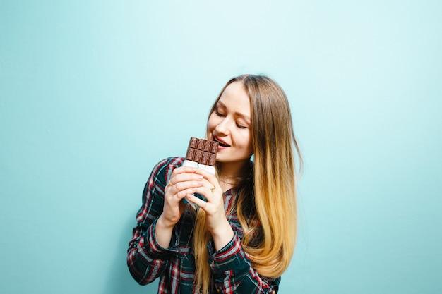 Ein porträt eines schönen blonden mädchens, das schokolade isst, wird auf einem blauen hintergrund aufgeregt
