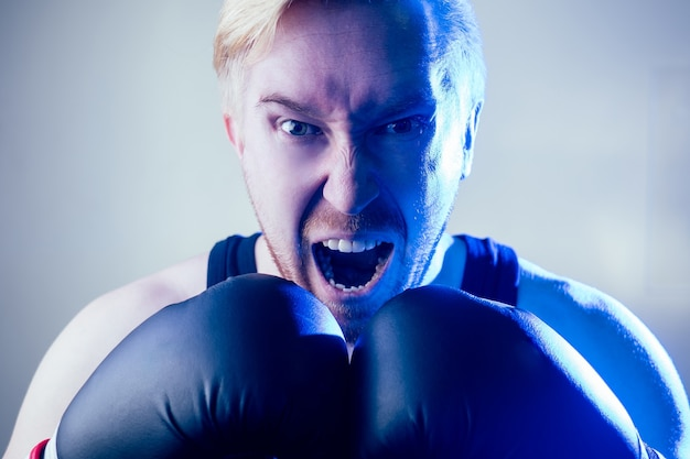 Ein porträt eines wütenden und bösen männlichen boxers, der sport im fitnessstudio macht. boxer und boxhandschuhe auf dunklem hintergrund. der mann schlägt zu. verband an den händen.