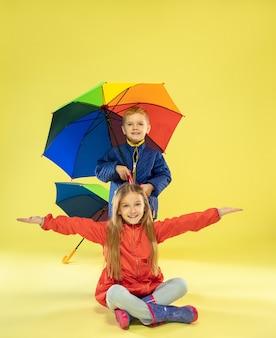 Ein porträt in voller länge eines hellen modischen kindes in einem regenmantel