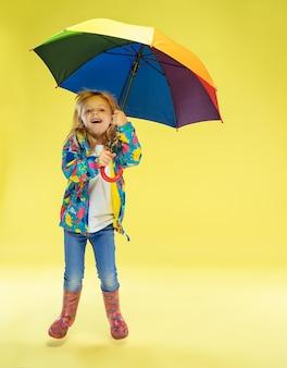 Ein porträt in voller länge eines hellen modischen mädchens in einem regenmantel, der einen regenschirm der regenbogenfarben auf gelber studiowand hält