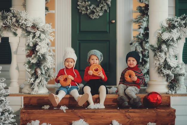 Ein porträt von kindern, die zusammen auf der veranda ihres hauses sitzen, essen bagels. frohe weihnachten, frohes neues jahr. hof mit einem weihnachtsbaum, lichtern und dekorationen. wunderzeit.