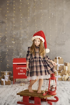 Ein portrait des schönen kindes, das auf dem schlitten auf geschenkhintergrund sitzt