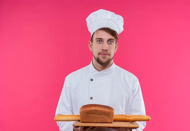 Ein positiver junger bärtiger kochmann in der weißen uniform, die ein hölzernes küchenbrett mit mehreren broten beim betrachten auf einer rosa wand hält