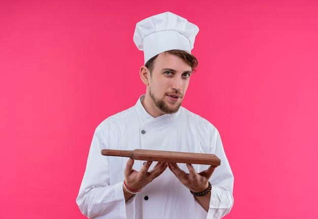 Ein positiver junger bärtiger kochmann in der weißen uniform, die hölzerne küchenbrett hält, während auf einer rosa wand schaut