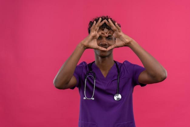 Ein positiver junger gutaussehender dunkelhäutiger arzt mit lockigem haar in violetter uniform mit stethoskop, das hände auf herzform hält