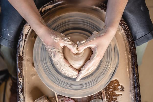Ein potter arbeitet in der werkstatt mit ton auf einem potterrad. frauenhände zeigen ein herzzeichen