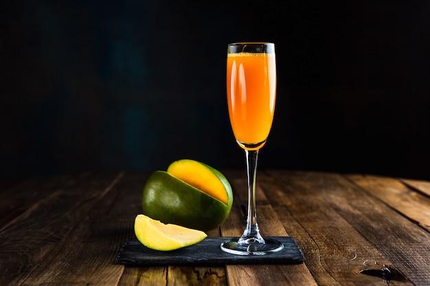 Ein prickelnder cocktail mit mango in einem flötenglas