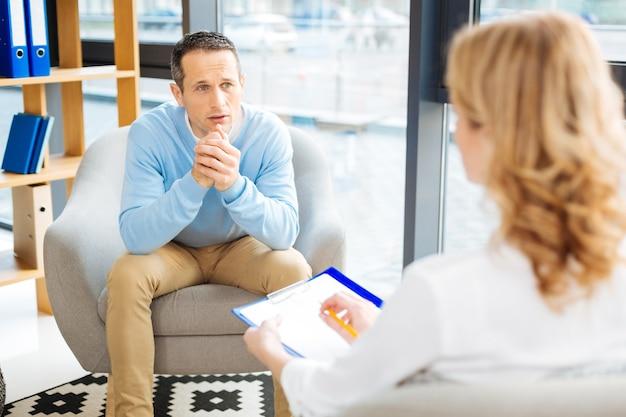 Ein problem teilen. trauriger unglücklicher düsterer mann, der seinen therapeuten ansieht und ein problem teilt, während er eine psychologische sitzung hat