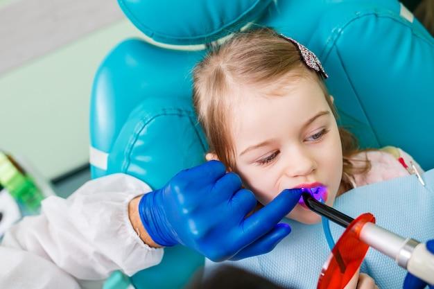 Ein professioneller arzt, ein kinderzahnarzt, behandelt die zähne eines kleinen mädchens mit instrumenten. zahnarztpraxis für patientenuntersuchung. der ablauf der zahnbehandlung bei einem kind