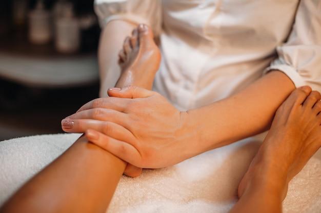 Ein professioneller arzt massiert die beine der klientin, damit sie sich entspannen und freude haben kann