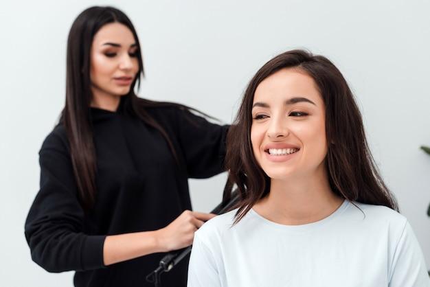 Ein professioneller, fokussierter stylist arbeitet mit einem lächelnden brünetten haar