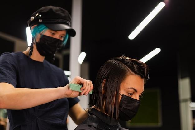 Ein professioneller friseur macht einen kundenhaarschnitt. das mädchen sitzt in einer maske in schönheit im salon