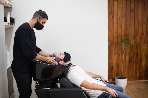 Ein professioneller friseur mit schutzmaske schneidet einem kunden während des coronavirus die haare