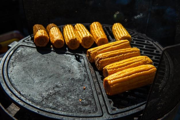 Ein professioneller koch bereitet mais auf dem grill im freien, essen oder catering-konzept zu