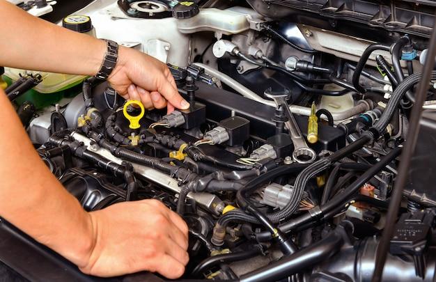 Ein professioneller mechaniker, der den automotor überprüft.