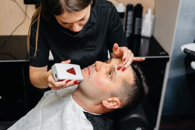 Ein professioneller stylist in einem modernen, stilvollen barbershop rasiert und schneidet einem jungen mann die haare