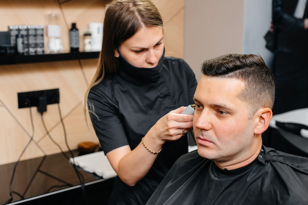 Ein professioneller stylist in einem modernen, stilvollen friseurladen rasiert und schneidet einem jungen mann die haare. schönheitssalon, friseursalon.
