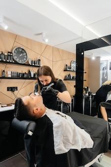 Ein professioneller stylist in einem modernen, stilvollen friseursalon rasiert und schneidet einem jungen mann die haare. schönheitssalon, friseursalon. Premium Fotos