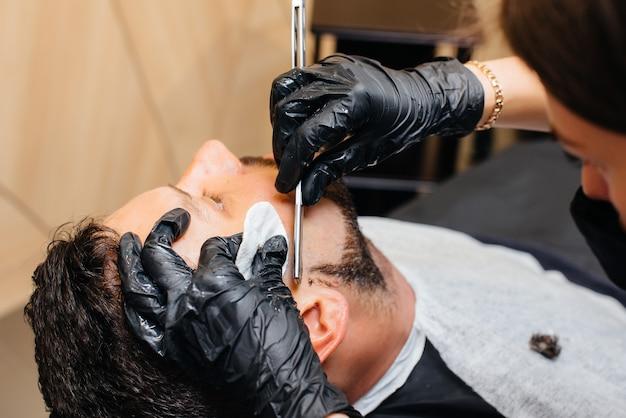 Ein professioneller stylist in einem modernen, stilvollen friseursalon rasiert und schneidet einem jungen mann die haare. schönheitssalon, friseursalon.