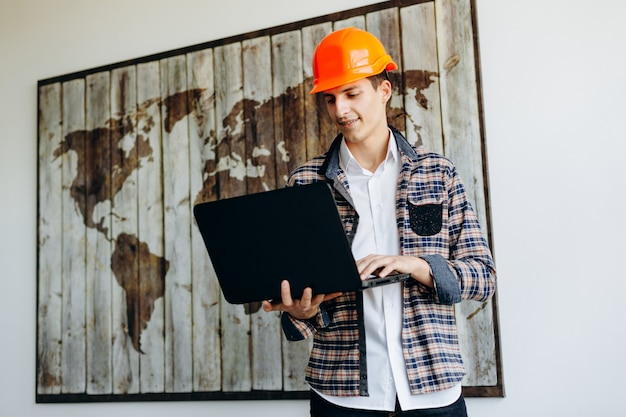 Ein professioneller vorarbeiter arbeitet in seinem büro an seinem laptop