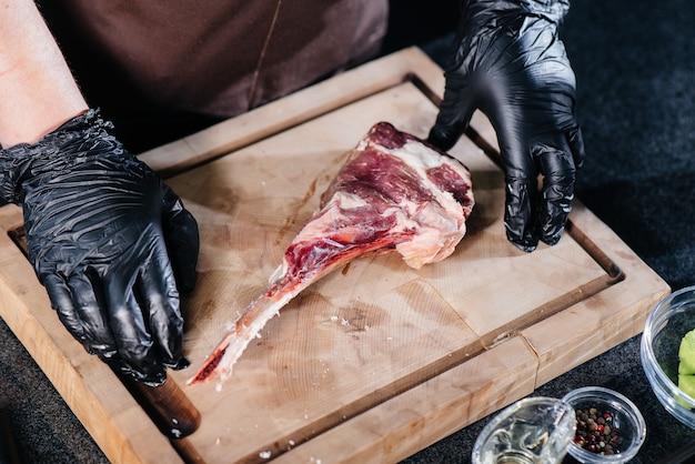 Ein profikoch mariniert und bereitet aus einem frischen stück fleisch ein saftiges steak zu