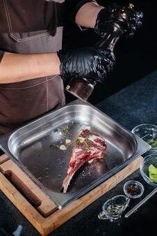 Ein profikoch pfeffert ein saftiges steak aus einem frischen stück fleisch