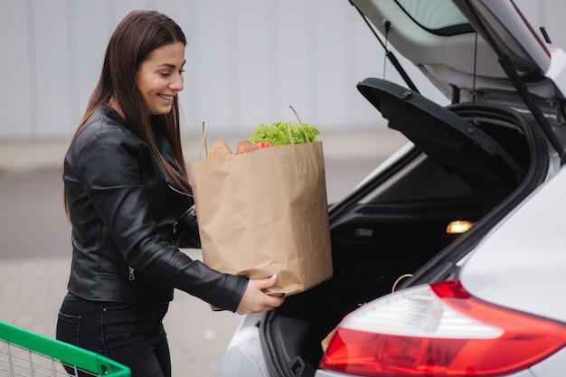 Ein prozess der jungen attraktiven frau, die lebensmittel von einem supermarkt vom wagen zum auto nimmt