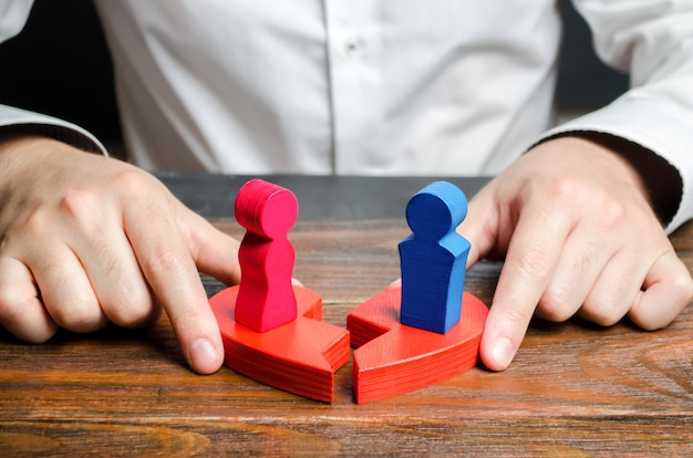 Ein psychologe verbindet die beiden hälften eines gebrochenen herzens mit figuren eines mannes und einer frau