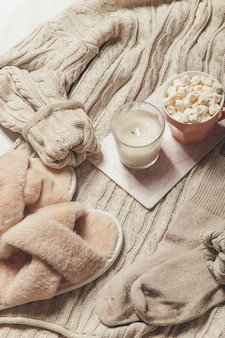 Ein pullover kaffee und eine kerze auf einem weißen hintergrund winter gemütliches bild