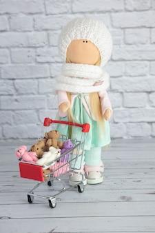 Ein puppenmädchen steht und hält einen einkaufswagen mit spielzeug und bunten plüschbären.