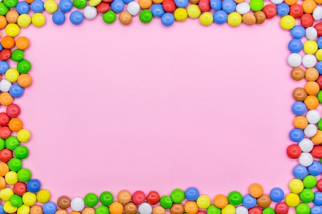 Ein rahmen aus bunten pralinen. großaufnahme der spitze, rosa hintergrund