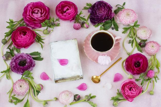 Ein rahmen aus einem hahnenfuß und einem buch, eine tasse kaffee