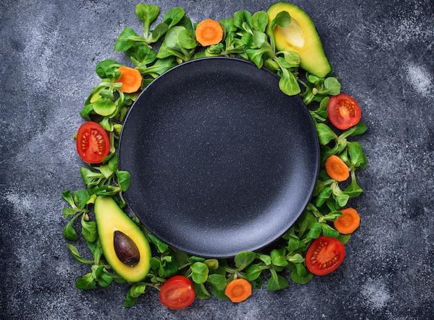 Ein rahmen aus gemüse rund um die platte.