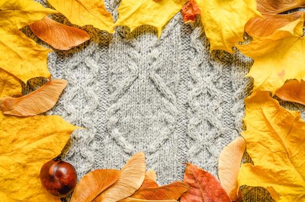 Ein rahmen aus herbstlichen orangefarbenen ahornblättern und samen und roter kastanie auf dem hintergrund eines gemütlichen grauen herbststrickwollpullovers. platz für text