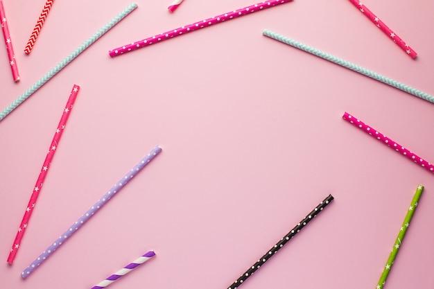 Ein rahmen aus mehrfarbigen cocktailröhren für text auf einer rosa oberfläche