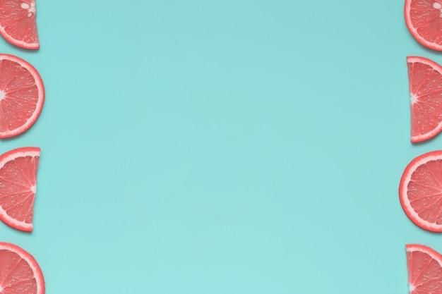 Ein rahmen von rosa zitrusfruchtscheiben auf hellem blauem hintergrund