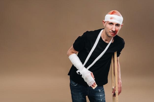 Ein ramponierter mann mit einem verbundenen kopf und einem gipsverband am arm steht auf krücken auf grauem hintergrund.